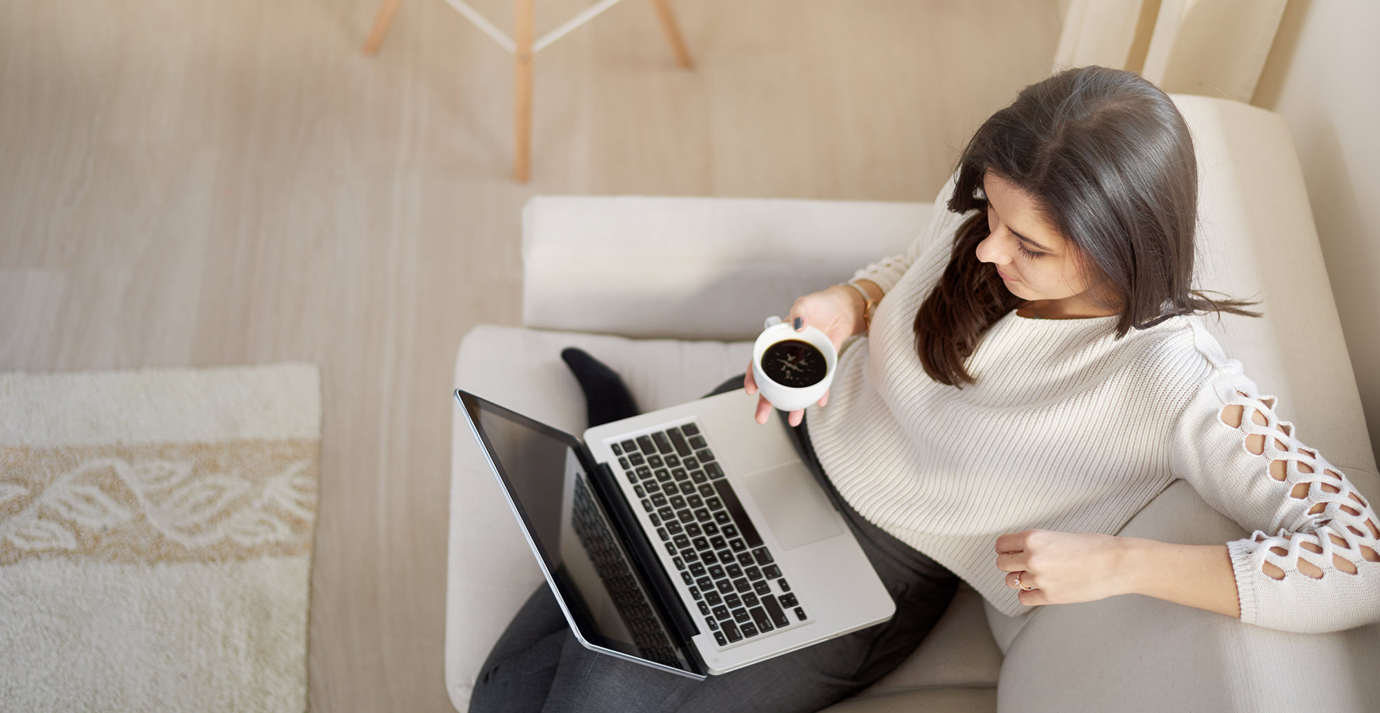 Woman using laptop for work and drinking coffee while sitting on sofa.