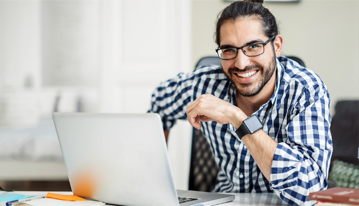 Man with glasses and beard at a laptop